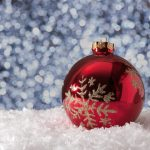 red Christmas ornament sitting in snow with snowfall in the background
